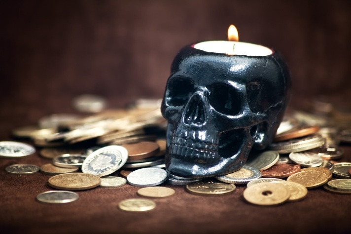 Close up skull candleholder with coins